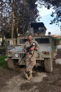 Former Marine Jamie Lane in front of abandoned Iraqi humvee