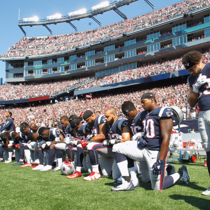 Players kneel before a football game. Image found on Business Insider.